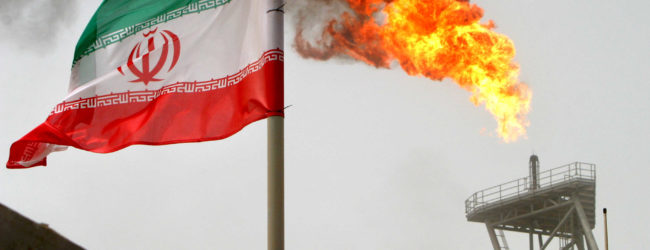 FILE PHOTO: A gas flare on an oil production platform in the Soroush oil fields is seen alongside an Iranian flag in the Persian Gulf, Iran, July 25, 2005. REUTERS/Raheb Homavandi/File Photo - RC123E3513F0