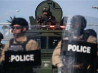 A Miami Police officer watches protestors from a armored vehicle during a rally in response to the recent death of George Floyd in Miami, Florida on May 31, 2020. - Thousands of National Guard troops patrolled major US cities after five consecutive nights of protests over racism and police brutality that boiled over into arson and looting, sending shock waves through the country. The death Monday of an unarmed black man, George Floyd, at the hands of police in Minneapolis ignited this latest wave of outrage in the US over law enforcement's repeated use of lethal force against African Americans -- this one like others before captured on cellphone video. (Photo by Ricardo ARDUENGO / AFP) (Photo by RICARDO ARDUENGO/AFP via Getty Images)